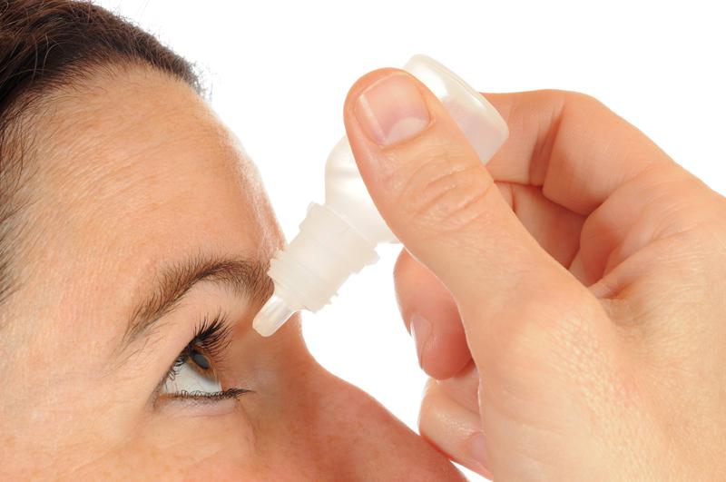 Foto von Frau bei der Anwendung von Augentropfen