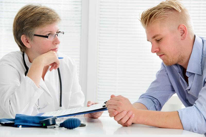 Foto von jungem Mann im Gespräch mit einer Ärztin